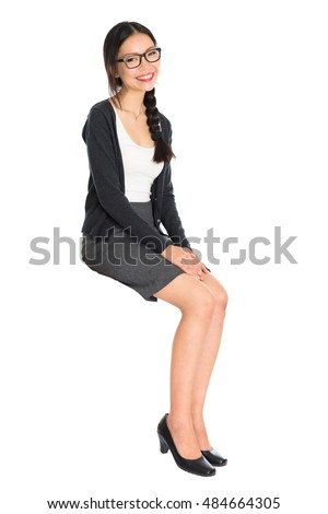 Full body portrait of young Asian woman sitting on invisible chair, isolated on white background.
