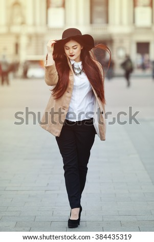 Full body portrait of young beautiful lady wearing stylish classic clothes walking at street of the old city. Girl looking down. Plus size model. Female fashion concept. Toned - stock photo