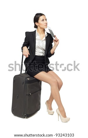 Full-body portrait of young business woman sitting on her black travel bag and holding the tickets with passport isolated on white background - stock photo