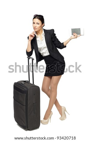 Full-body portrait of young business woman standing with black travel bag and holding the tickets with passport isolated on white background - stock photo