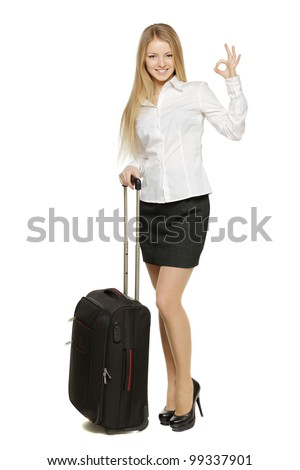 Full-body portrait of young business woman standing with black travel bag showing OK sign, isolated on white background - stock photo
