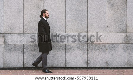 Full body portrait of young businessman walking against wall. Defense District. Paris, France.