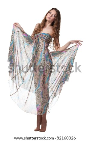 Full-body portrait of young charming female in chiffon dress posing over white background - stock photo