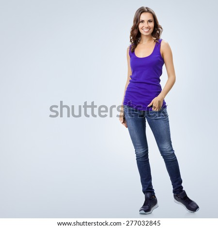 Full body portrait of young cheerful smiling woman in violet smart casual clothing, against grey background, with blank copyspace area for slogan or text - stock photo