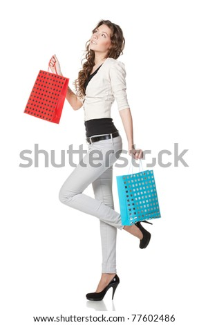 Full-body portrait of young elegant female holding paper-bags with purchases looking upwards isolated on white