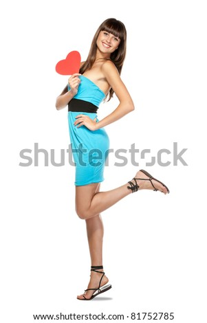 Full-body portrait of young female in blue dress holding heart shape isolated on white background - stock photo