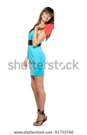 Full-body portrait of young female in blue dress holding heart shape isolated on white background