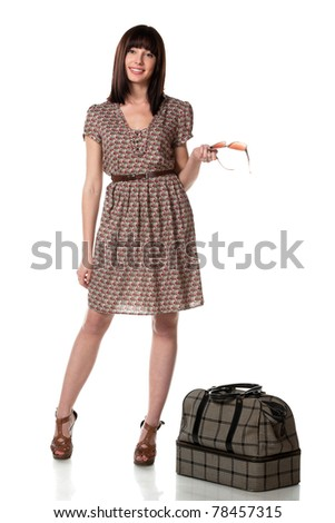 Full-body portrait of young female in dress standing near her travel bag isolated on white background - stock photo