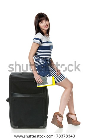 Full-body portrait of young female sitting on her black travel bag and holding the tickets with passport isolated on white background - stock photo