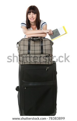 Full-body portrait of young female standing near her travel bags, holding passport and tickets isolated on white background