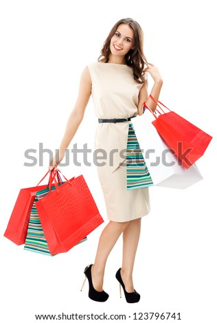Full body portrait of young happy smiling woman with shopping bags, isolated over white background