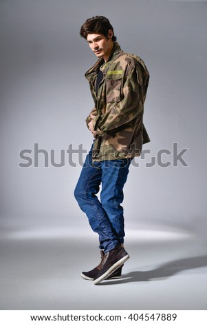 Full body portrait of young man dressed casual on light background - stock photo