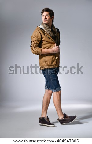 Full body portrait of young man in coat standing. Isolated on light background - stock photo