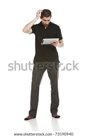 Full body portrait of young man scratching his head while looking at a digital tablet computer - stock photo