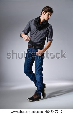 Full body portrait of young man walking in studio on light background - stock photo