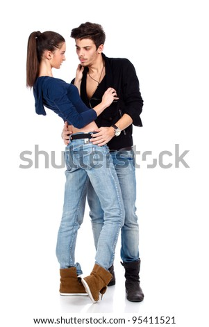Full body shot of a couple hugging and flirting, wearing jeans. Isolated on white background. High resolution studio image - stock photo