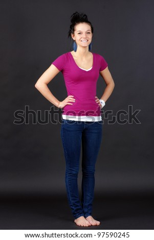 Full body shot of a natural beauty: casual young woman or student, in jeans and pink T-shirt over black background. - stock photo