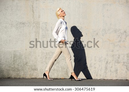 Full body side portrait of a cheerful young woman walking outside - stock photo