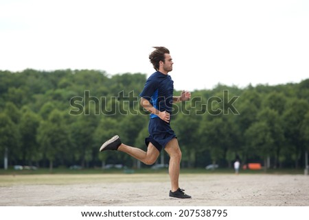 Full body side view of an athletic young man running outdoors - stock photo