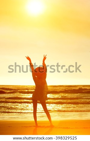 Full body silhouette from behind of a young woman standing at beach with hands raised peace signs