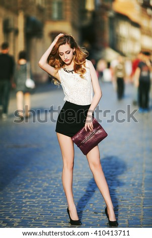 Full body street fashion portrait of a young beautiful confident woman posing on the urban background. Model looking down. Girl wearing stylish clothes. City lifestyle.  - stock photo