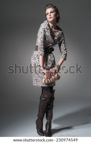 Full body Studio portrait of a young woman with a purse posing on light background - stock photo