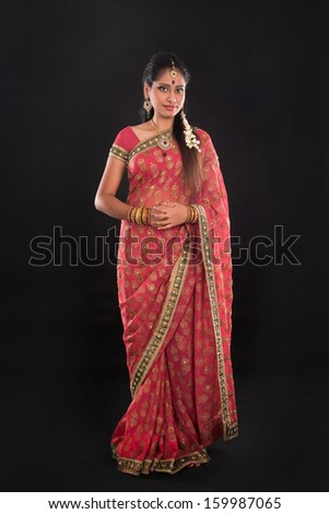 ... Indian girl in sari costume standing isolated on black background