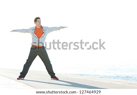 Full body view of a sports man stretching his arms and legs in a star shape while standing on a racing track by the blue sea, with a sunny sky in the background. - stock photo