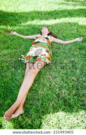 Full body view of a young woman laying down on green grass with her arms outstretched, relaxing while feeling nature during a sunny summer day, outdoors. - stock photo
