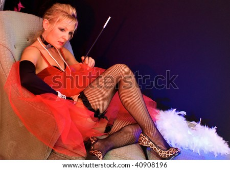 full body view of beautiful blonde laying on sofa. Actress dressed up as old fashioned madam or prostitute can also be a sexy mrs. claus or santa's elf for christmas.  Shot with blue and red strobes. - stock photo