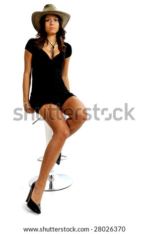 Full body view of sexy cow girl wearing short black elegant dress, sitting on a stool. Isolated on white background. - stock photo