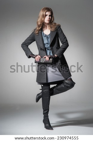 Full body young blonde girl in black coat wearing bag posing gray background - stock photo
