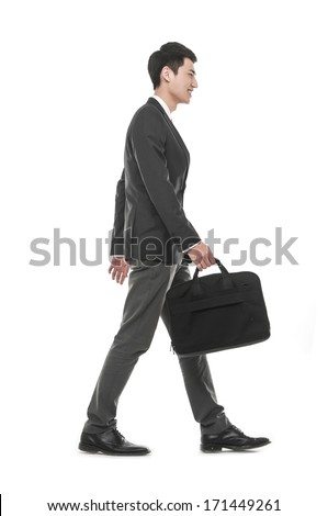 Full body young business man holding a laptop bag walking in studio - stock photo