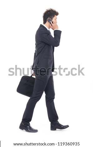 full body young business man walking carrying a suitcase speaking on cellphone - stock photo