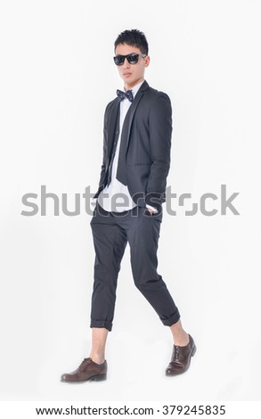 Full body young businessman in sunglasses walking in studio - stock photo