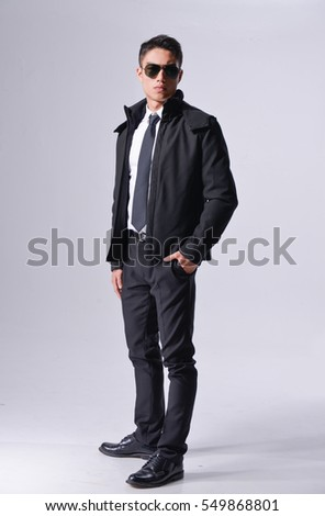 Full body young businessman standing on gray background