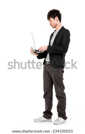 Full body young businessman using laptop computer, standing,