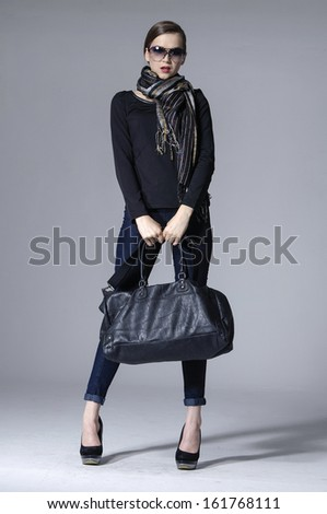Full body young elegant woman in sunglasses with scarf holding bag posing - stock photo