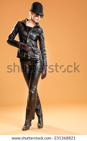 Full body young fashion model in sunglasses with hat posing in the studio