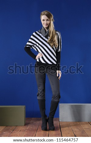 full body young fashion model posing with cube on blue background
