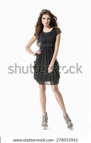Full body young girl wearing black sundress posing in studio - stock photo