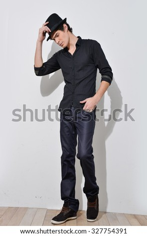 Full body Young mal model posing with hat in the studio - stock photo