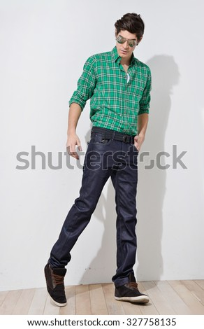 Full body Young mal model with sunglasses walking in the studio - stock photo