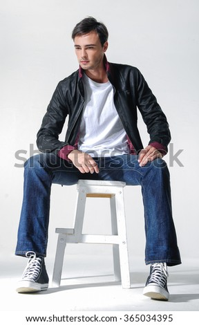 Full body young man in jeans sitting wooden cube   - stock photo