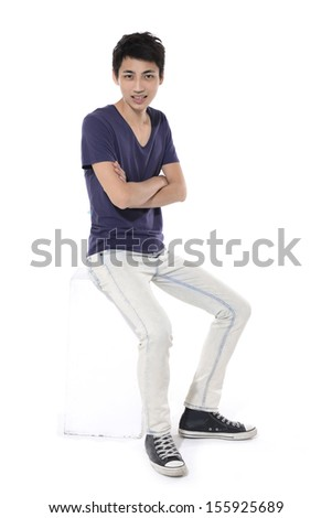Full body Young man with hands sitting cube  - stock photo
