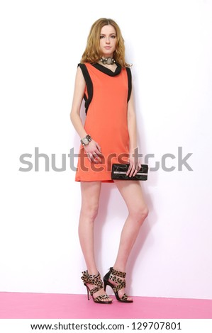 Full body young woman holding bag posing in studio