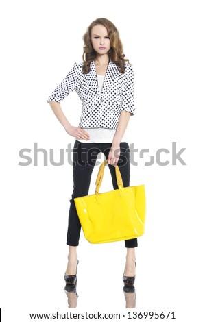 Full body young woman holding yellow bag posing in studio - stock photo