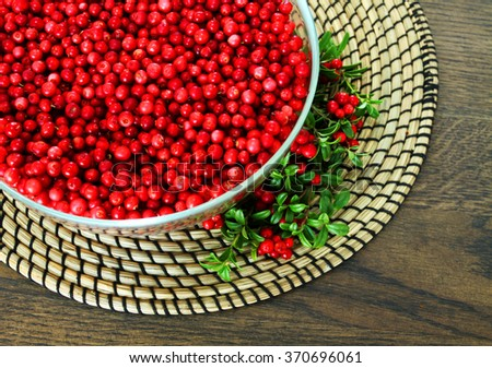 Full bowl of cowberries on wooden background - stock photo