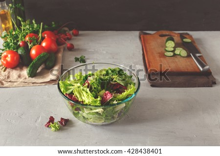 Full bowl of fresh green salad on a light table on a rustic kitchen. Concept helpful and simple food - stock photo