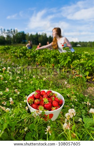 Full bowl of strawberries. Focus on bowl and group of girls behind, vertical format - stock photo